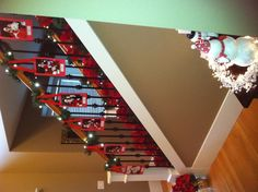 Photo only: Display yearly Santa photos on stair railing. My husband liked this idea so much that he  did it for me. He just used red construction paper for the backing and cut slits for the ribbon. I want to eventually get lightweight red velvet frames.