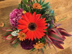 Centerpiece with bright Red Gerbera Daisy taking center stage, supported by leucodtendron, mini mums, and dianthus.