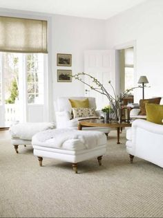 Perfect living room:  neutrals; white furniture; natural roman shades; comfortable ottomans on casters; French doors; sisal rug; chartreuse pillows; cocktail table