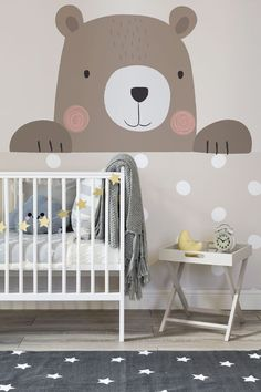 Peek-a-boo! This nursery wallpaper design features an adorable cartoon bear alongside giant polka dots. Lovely taupe brown hues make for a stylish yet calming nursery space.