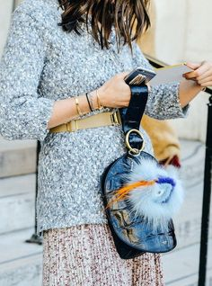 Grey sequin sweater, Fendi bug, Cartier bracelet, red and white knit skirt