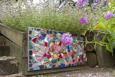 A mosaic of broken dishes brightens the garden during the winter months. Lavender phlox grows in front and cat mint behind the piece.