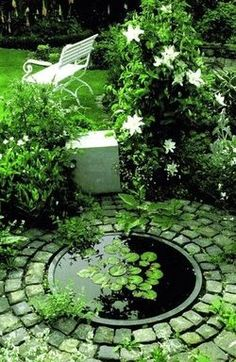 Circular water feature with flowering vine and lawn. In Birmingham, AL, get awesome sprinkler service from BlueSkyRain.com and landscape lighting too. #irrigation #garden #Waterfeature