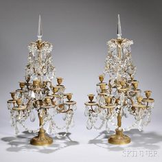 Pair of Louis XVI-style Twelve-light Bronze Candelabra, late 19th/early 20th century, each with colorless, faceted glass hanging - Estimate: $400 - $600