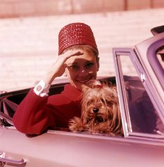 The actress Audrey Hepburn photographed with Mr. Famous in her car by Pierluigi for a fashion editorial in Rome (Italy), in March 1961.