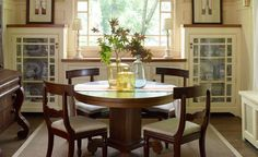 Rich wood dining furniture grounds this warm and welcoming space. On the tabletop, a grouping of colored glass bottles creates a shimmering centerpiece. Flanking the window, custom built-ins with glass-front doors contain vintage blue transferware.