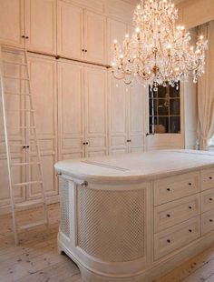"""Love the island.   Gorgeous closet pictured in the book, Wood at Home: """"The dressing [room] was made in solid Tulpier wood and the inside in Sapeli wood. The bent walls are steamed and finished with mouldings in a warped 'profil contre profil.' """" #chandelier #closet #dressing_room #woodwork"""