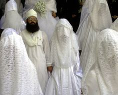 PALESTINIAN BRIDE.....ON INTERNATIONAL BUSINESS TIMES.......PARTAGE OF ANGELIQUE GALLEGOS SANCHEZ....... A Muslim groom stands with his veiled brides with other couples before a mass wedding in Amman July 19, 2002.