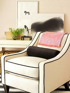 White upholstered chair w/ black piping. So pretty and classy.