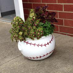 DIY…make a baseball planter…use any round planter..paint it white..add on the baseball stitching.   :-)