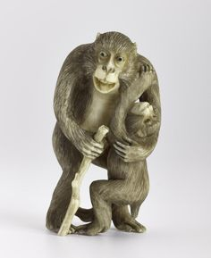 Netsuke of carved ivory, a monkey with a stick in his right hand and his left arm round a smaller monkey, unsigned: Japan