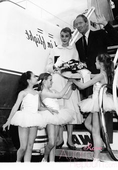 Tiny ballerinas from the Paris Opera give a big welcome and a bouquet to actress Audrey Hepburn as she arrives at the Paris airport with her husband, actor Mel Ferrer. Audrey's in the French capital to film a Hollywood movie called Funny Face, June 2, 1956.