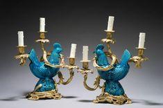 Paire de candélabres à trois lumières en bronze ciselé et doré. Ils sont à décor au centre de coq en grès émaillé turquoise, dans le goût de la Chine. Bases rocailles. Style du XVIIIe siècle H: 40 - L: 40 cm