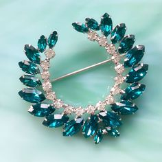 This vintage 1960s signed B. David teal and clear rhinestone laurel leaf / wreath pin or brooch has a depth of color not seen in contemporary jewelry. Prong set marquise & chaton stones are set in a light-weight rhodium-plated finish. With its flat back, it would be ideal for a wedding brooch bouquet or a bridal hair comb. Its in like-new, unworn vintage condition with lots of fire and sparkle. Vintage jewelry is always in style and makes the perfect romantic gift for her. Repeat c...