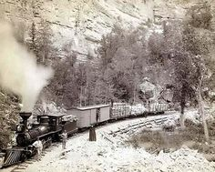 """""""Giant Bluff."""" Elk Canyon on Black Hills and Ft. P. R.R.. It was created in 1890 by Grabill, John C. H., photographer.    The photograph presents A wood-burning locomotive with four cars, on a track below a cliff; several people are posing in front of the train."""