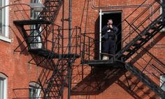 Homan Square protest An officer appears to film protesters from a fire escape at Homan Square. Photograph: Chandler West/the Guardian Crowd gathers outside facility at centre of claims of unconstitutional abuse Anonymous and Black Lives Matter among groups represented