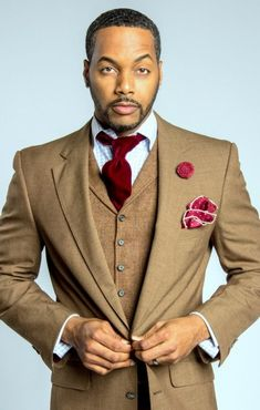 Men's brown three piece suit with red tie, pocket square, and lapel flower.