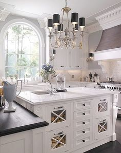 Love this kitchen- everything from the chandelier to the glass panelled island with storage and the giant window. It's stunning.