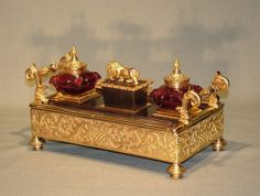 A mid 19th Century Regency period bronze and ormolu Pentray, having cranberry cut-glass inkwells flanking central wafer box, the lid mounted with well cast lion. The Pentray having bold leaf scrolled carrying handles above fretted frieze decorated with baskets, flowers, pineapples and leaf scrolls supported on ring-turned feet.