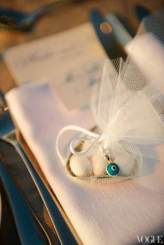 Bombonieres, a traditional party favor, are given at almost every Greek wedding. Candy-covered almonds in a silver dish are wrapped up with white tulle. Attached to the white ribbon is a mati, or evil eye, a Greek talisman and the perfect parting gift.