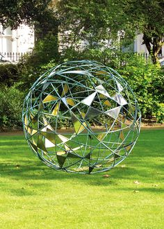 David Harber | Matrix sphere in the garden | The sculpture consists of random bronze hoops forming a sphere of 1.7metres in diameter with random stainless steel petals. The metal petals are mirror polished on the outside, reflecting both the greenery of the surroundings and the blue of the sky.The inner surface of the steel petals is covered with 23¾ gold leaf creating a shimmering orb of floating gold petals.