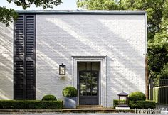 """To """"update and clarify"""" a 1961 house in Houston, architect Ray Booth of McAlpine and Elizabeth Kennedy balanced the original aesthetic with a contemporary point of view. Booth tweaked the '60s white-brick facade with new vertical shutters and added a steel-gated front door and custom lantern."""