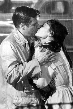 Holly Golightly (Audrey Hepburn) and Paul Varjak (George Peppard) kissing in the rain in Breakfast at Tiffany's :) Such a timeless and romantic scene