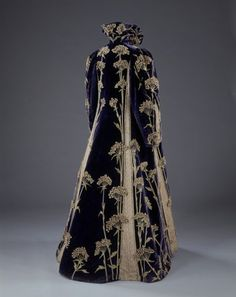 Embroidered velvet coat  Marshall & Snelgrove Ltd (retailers)  1895-1900  London  Embroidered velvet, satin and lace  Museum no. T.49-1962  Given by Mrs A. Poliakoff    This Paris couture coat reflects the influence of the European Arts and Crafts Movement. It features a medieval-style collar and is entirely covered in dramatic sprays of an English wildflower called 'Sweet Cicely' hand-embroidered in yellow and green silk, with petals of white felt.    The influence of the Arts and Craft...