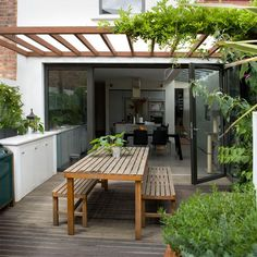 Quintal pequeno. Pérgola de madeira e plantas logo darão a sombra tão desejada. Mesa e bancos de madeira ficam bem em qualquer lugar.