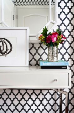 What's black and white and patterned all over? The incredible bold wallpaper in this entryway, setting the scene for a fashionable vignette of fresh flowers and pretty books. While the wall covering makes a big statement alone, the white furnishings, accents and pop of color really tie everything together.