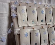 Advent calendar. Materials: paper tubes, corkboard, lace/ribbon, tiny clothespins, snowflake hole punch and blue security envelopes (to punch out the snowflakes)