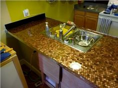 Kitchen counterop tiled with pennies . You could also use pennies to tile a floor or a table. Penny Countertop, Countertop Makeover, Concrete Countertops, Kitchen Countertops, Backsplash, Outdoor Countertop, Tops Diy, Copper Penny, Up House