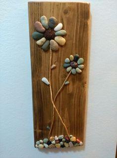 Flores con piedras y ramas secas, sobre madera reciclada.