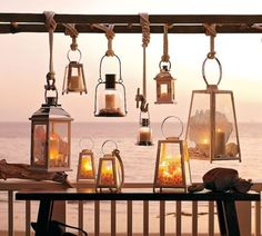 Love lanterns for the outdoors. Cluster of lanterns + nautical rope knots + filled with sand, shells, and candles.