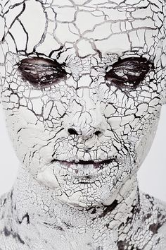 Cracks of face mask/make-up. Looks like something heaving was applied that physically cracked, but the same effect could be done with painted lines only...