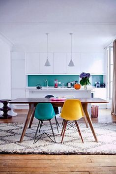 Great colorful dining room and kitchen with eames chairs and moroccan style rug