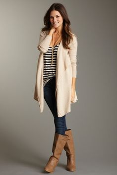 Long cream cardigan, striped shirt, medium wash skinny jeans, and light brown leather boots with gold accessories