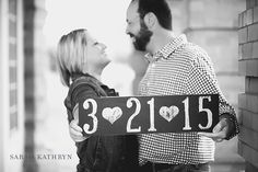 Outdoor engagement photos with couple holding up custom wooden sign with wedding date on it - Photo by Sarah Kathryn Portrait Design