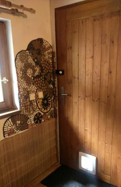 wall mosaic by the entrance door, made of handmade ceramic tiles in combination with gemstones and broken bathroom tiles