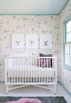 Nursery with feminine wallpaper, art, and painted trim