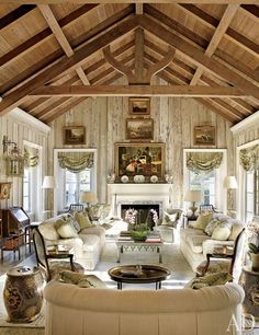 The living room's pecky-cypress paneling was lightened by decorative painter Bob Christian, whose work can also be seen on the tile fireplace surround. The landscape paintings are 19th-century English, the roll-arm sofas are by O. Henry House, and the Louis XV–style armchairs by Edward Ferrell + Lewis Mittman, in the foreground, are upholstered in a Brunschwig