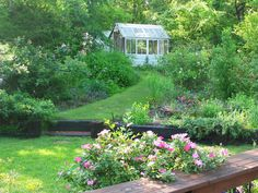 A wide green path through antique roses and butterfly-attracting plants leads to this cottage-style greenhouse.