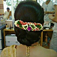 thai wedding hairstyle low updo accessorized with beautiful floral garland