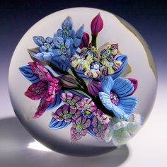 """PETER MCDOUGAL FLORAL PAPERWEIGHT. Floral bouquet consisting of six millefiori flower blossoms and five lamp worked buds on a clear ground. Signed with a """"P MCD"""" signature cane. SIZE: 3"""" dia x 2-5/8"""" t. PROVENANCE: Barry Schultheiss Collection, James Julia auction 2010."""