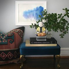 Footstool as side table / art hung low on wall