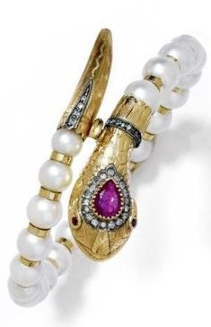 """PEARL AND GEMSTONE BANGLE, ca. 1920. Fancy snake bangle, the clasp designed as a finely engraved snake""""s head, decorated with a drop-cut ruby, within a border of 30 small single-cut diamonds, the finely engraved snake""""s tail decorated with 4 small single-cut diamonds. The bangle of 22 cultured pearls alternately strung with gold intermediate rings.:"""