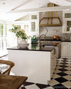blk/wht kitchen:  floors and cabs, hood, beams, brass accents on vent hood - an estate home in Litchfield county