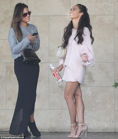 Got the giggles: Cara and Pia laugh together outside the restaurant as Cara puffs away on a cigarette