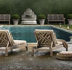 Love the idea of a concrete fountain at the end of a long pool with tall shrubs behind it.