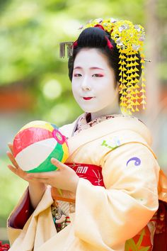 The first-year maiko Kanako with a paper ball! She still looks like a young girl but I think that when she grow up she will be a charming woman! (Source)